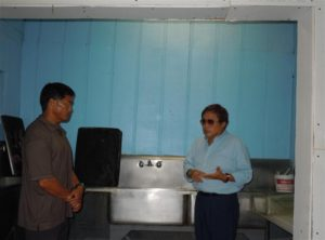 Bakery owner George Kanemitsu, right, speaks with DOH inspector Dean Kagawa at the bakery's washing station. Photo by Catherine Cluett