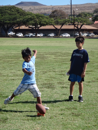 Naea Starkey, 8, and Owan Svetin, 8, practice their punts before the competition.