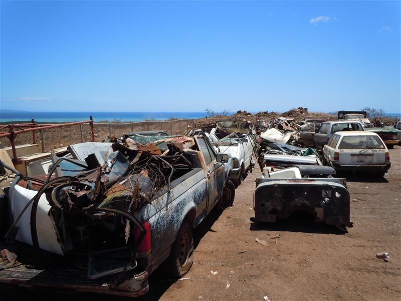 Junk cars wait to be crushed before being transported to Oahu for recycling. Photo by Catherine Cluett