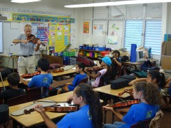 Bob Underwood teaches violin to Kualapu`u students during a 21st Century Music class last year