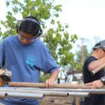 Ninth grader Kai Kalani grinds down poles for the racks.