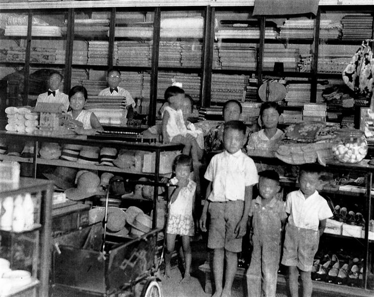 Inside Misaki's in its original building, showing hats, cloth, shoes and other items for sale. Back row left to right: Friend and store clerk Masato Yoshiyoka, sales clerk Margaret Matsumura, Masataro Misaki, Uta Misaki (seated) holding daughter Irene, friend Mrs. Nishiyama, Clara (Misaki); front row Misaki children Eileen, Richard, Tadashi and Mike. Photo courtesy Irene Iwane.