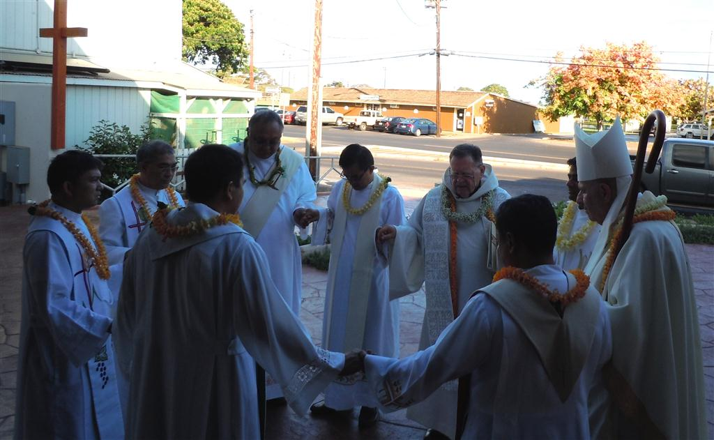Father Petrie and visiting priests pray before mass last week